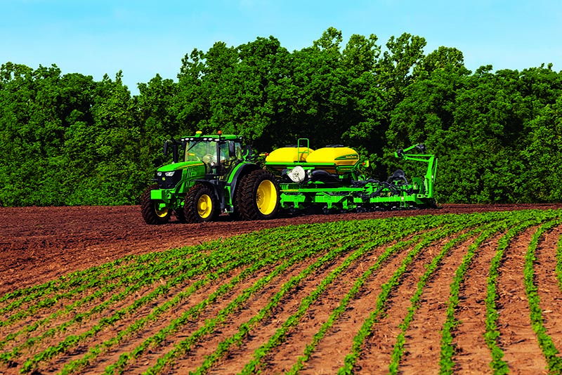 A John Deere tractor pulling a sprayer in a field of soybeans