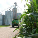 combine parked beside corn field and grain elevator