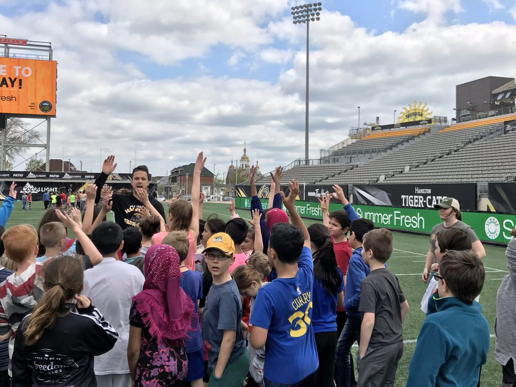 Kids raise their hands with a Tiger Cats player on the field