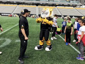 Kids and mascot listening to a Tiger Cats player