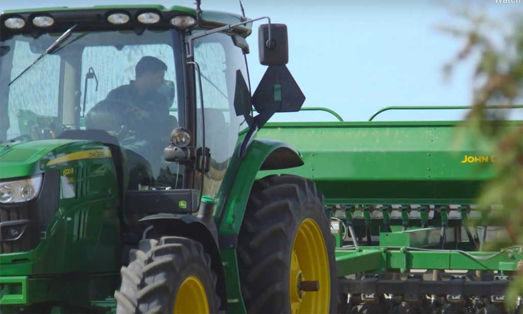 a man driving a green tractor