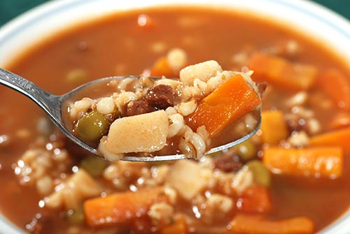 A close up of a spoonful of beef and barley soup