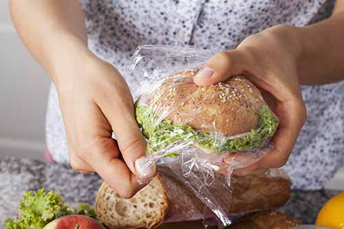 A sandwich in a plastic bag being unwrapped by hands