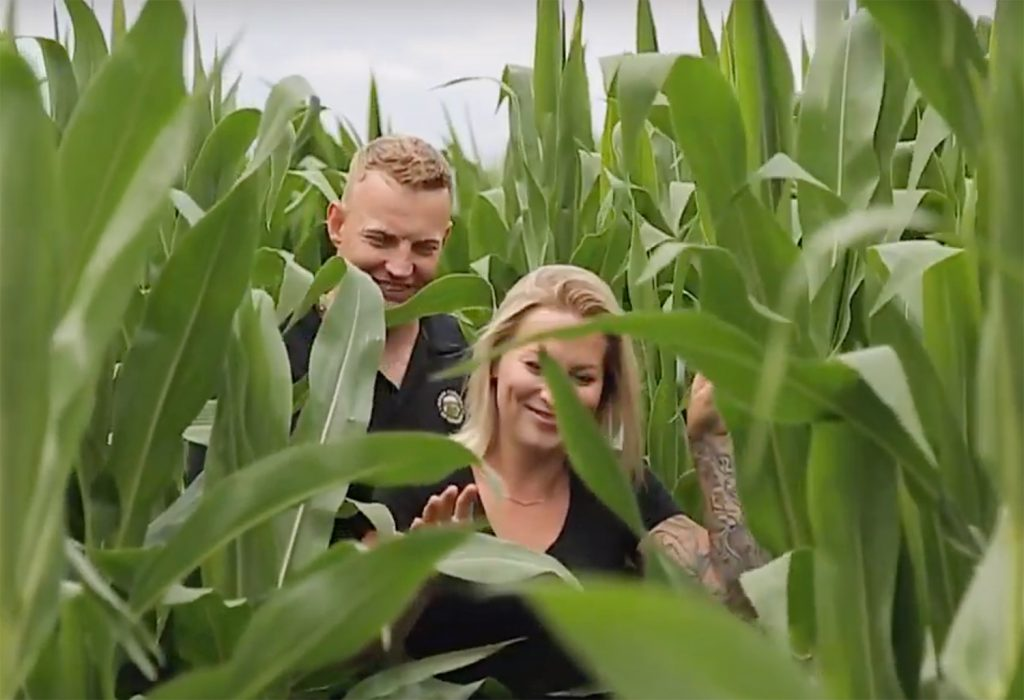 a man and a woman walking through a corn field towards the camera