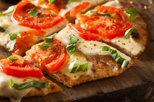 a thin-crust pizza with tomatoes and basil