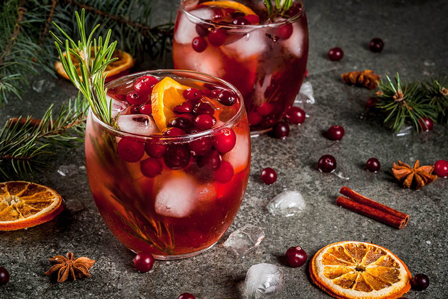 Holiday Cocktail with Ontario Whiskey cranberry, rosemary and garnished with oranges, cinnamon sticks and cranberries