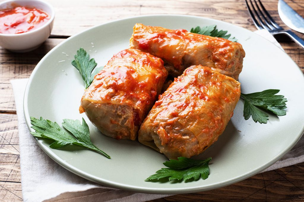 Cabbage rolls with pork, barley and vegetables on the plate. Stuffed cabbage leaves with meat. Wooden background