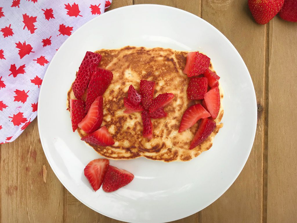 pancakes decorated to look like the Canadian flag using cut strawberries.