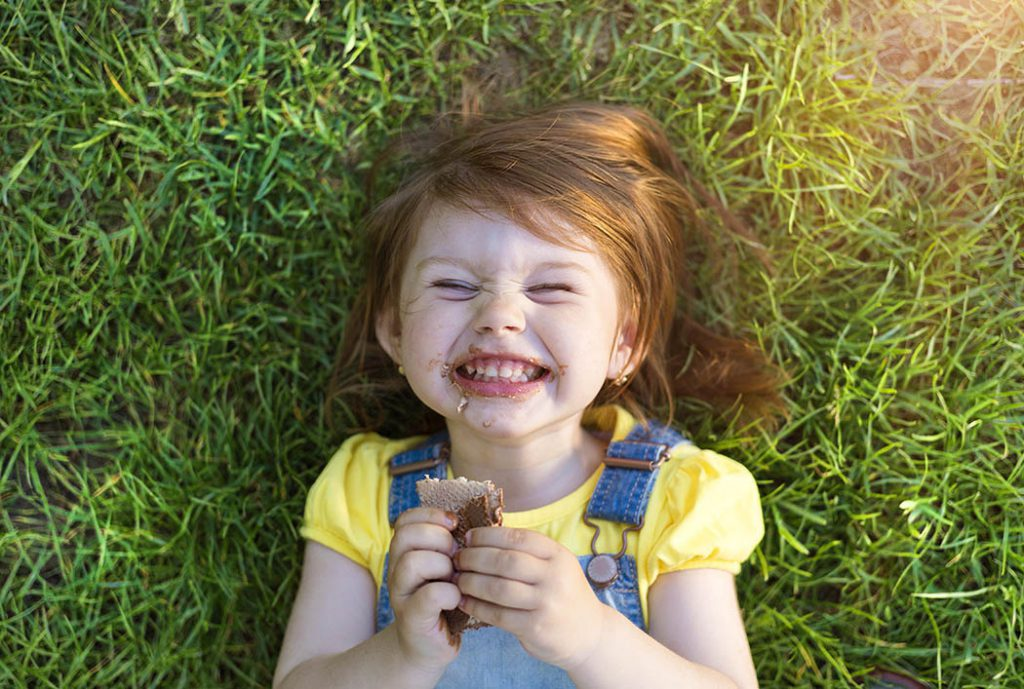 little girl eating wheat crackers in grass