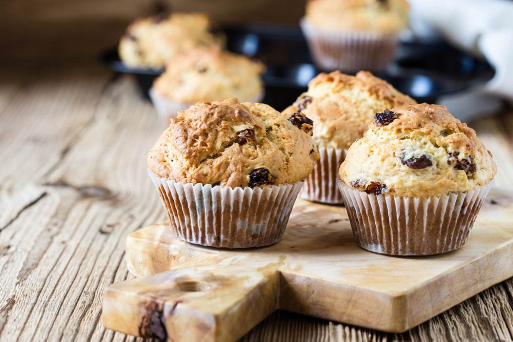 breakfast cornmeal muffins with raisins on a wood serving platter on a wood table.