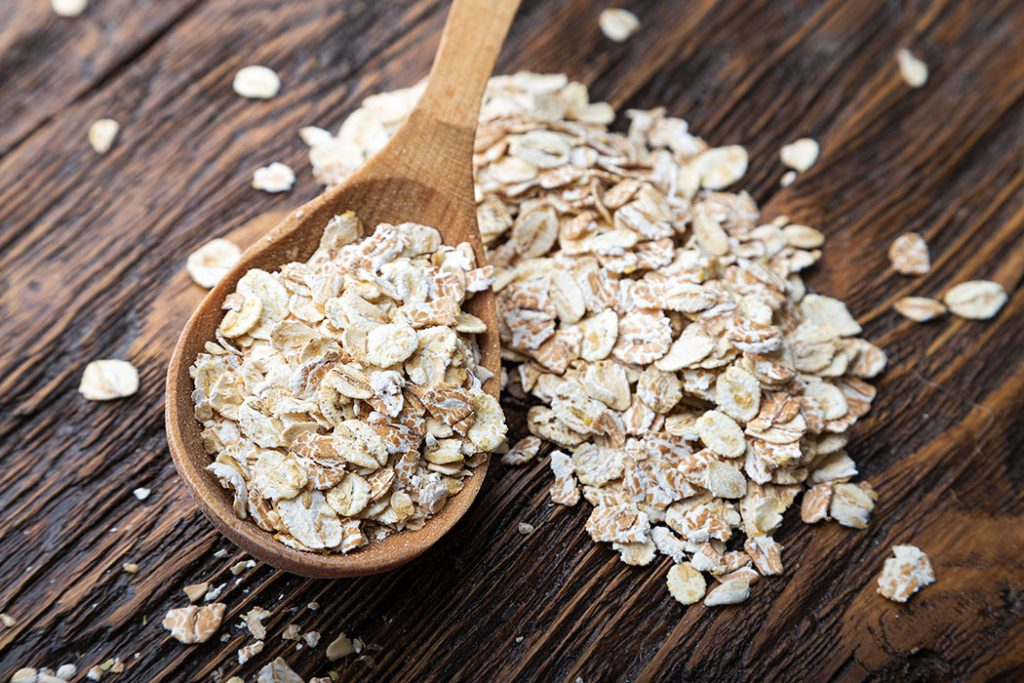 raw oatmeal flakes on wood spoon on wooden table