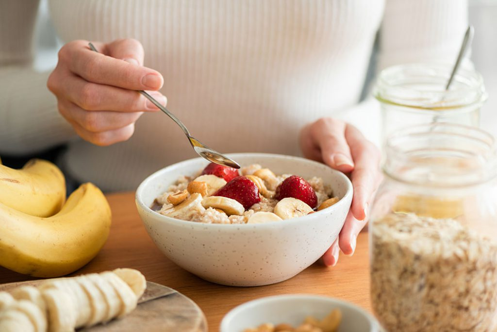 Bowl of oatmeal topped with chopped bananas, strawberries, and nuts.
