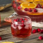 cranberry whisky cocktail with frozen cranberries and orange slices