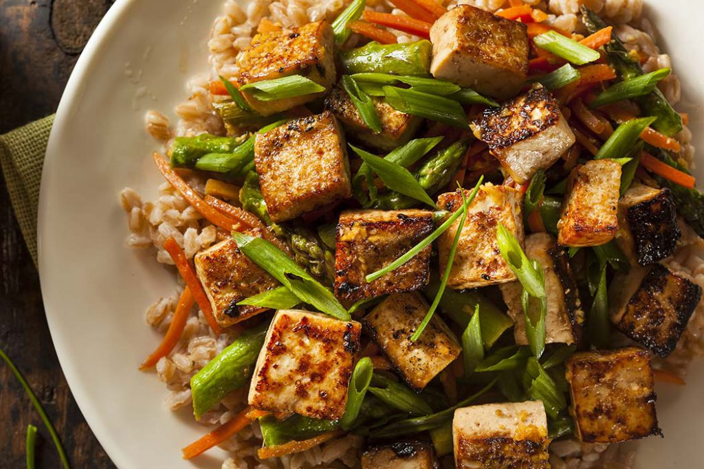Sriracha flavoured tofu on a plate of coconut rice, asparagus and carrots.