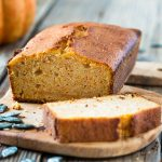 Homemade pumpkin bread baked in a loaf pan on a wooden board
