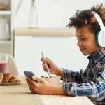 African boy in headphones using his mobile phone while eating breakfast in the kitchen
