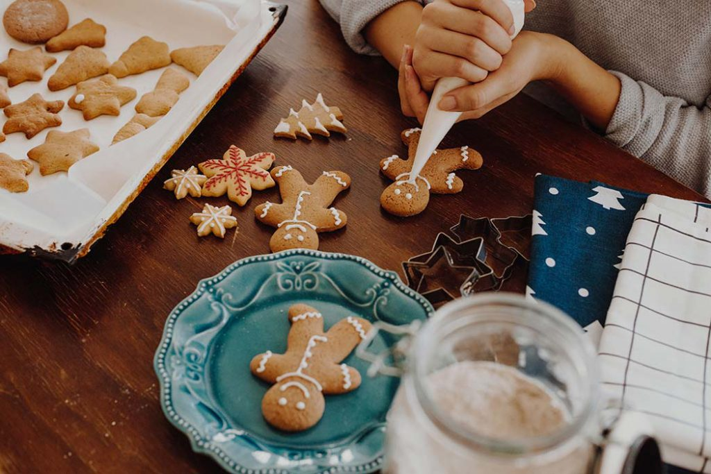 women decorating homemdae gingerbread Christmas cookies.