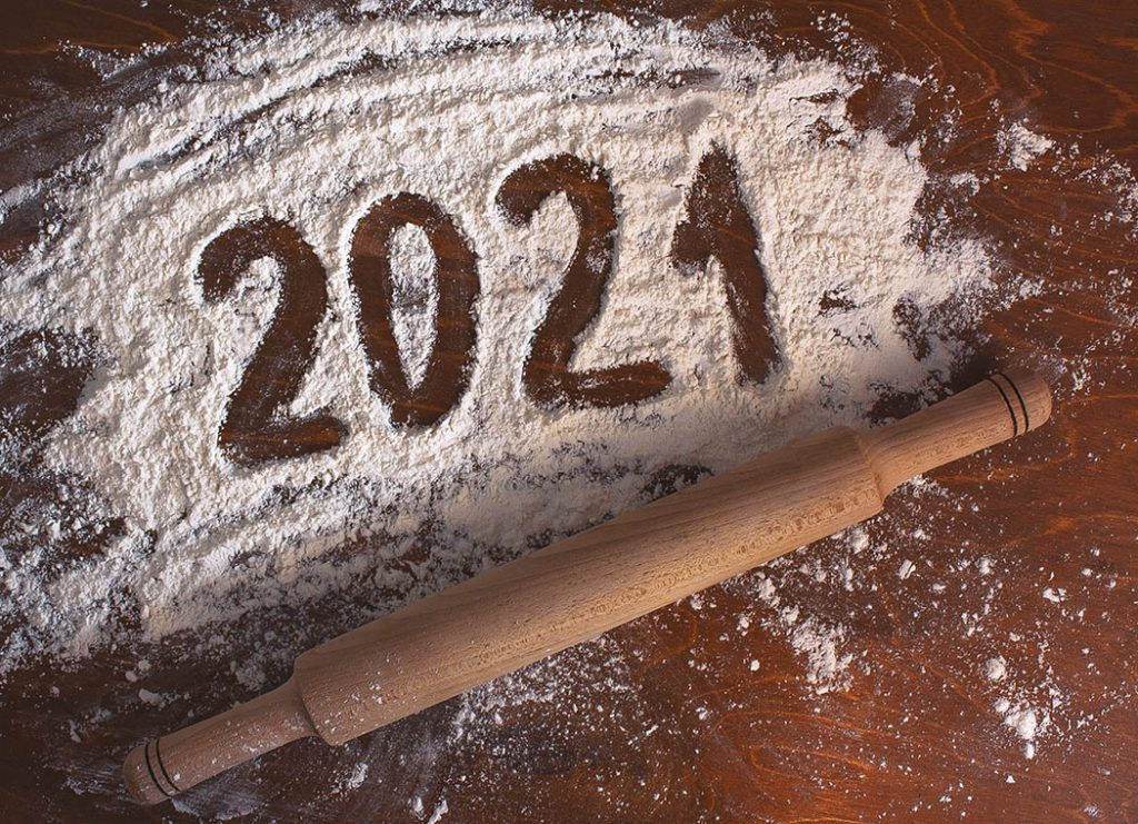 2021 written on white flour on a wooden table with a rolling pin.