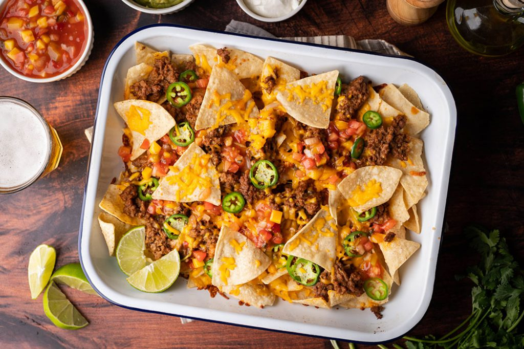 corn chip nachos with colourful toppings in a white sheet pan.