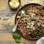 Whole wheat fusilli pasta with mushroom and spinach on a dark plate over old rustic wooden background.Top view with copy space.