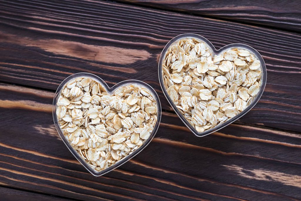 Raw oat-flakes on dark wood board background. Dry uncooked cereal in two bowl at heart shaped