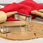 Dog biscuit dough with rolling pin and bone shaped cookie cutters on a silicone mat.