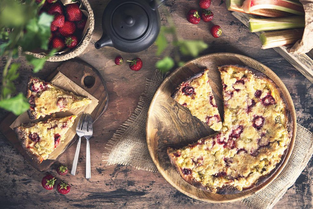 Rhubarb crumble pie with strawberry on rustic wooden table with fresh rhubarb, berries, plant. Beautiful still life homemade dessert. Top view, flat lay. Natural light at kitchen, organic products.